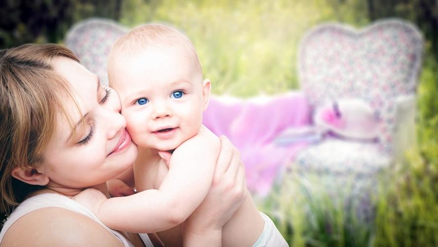 anyai szeretet látszik a nőn, ahogy a kezében tartja kisbabáját