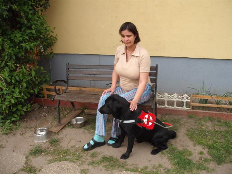 fekete labrador vakvezető kutyájával ül egy padon egy hölgy