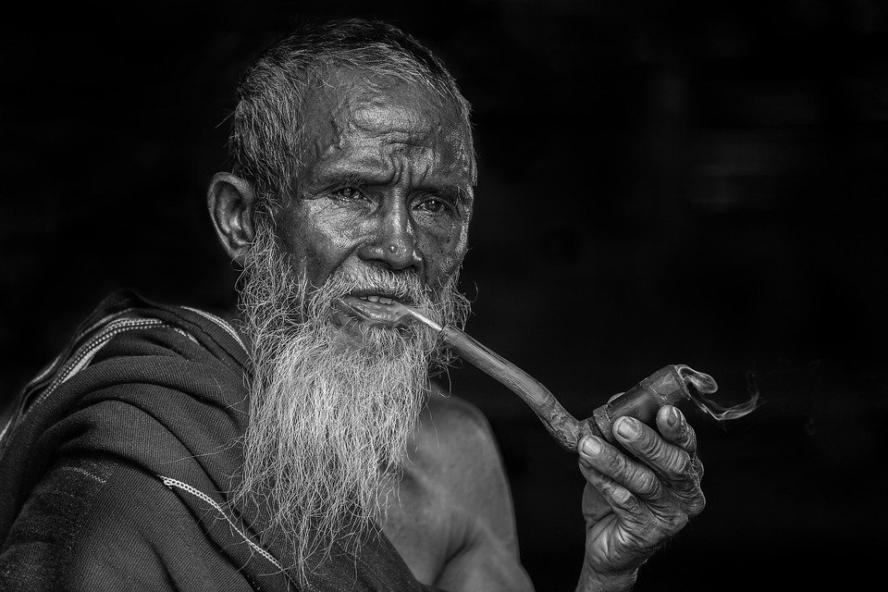 Szakállas rendezetlen külsejű pipázó idős ember