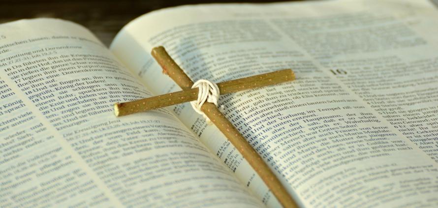 nyitott biblia, rajta két ágacskából készült kereszt